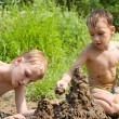Two children build a sand castle — Stock Photo