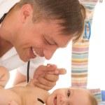 Man doctor examining newborn — Stock Photo #5515042