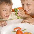 Beautiful boys holding a plate with vegetables - Stock Photo