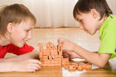 Brothers are building of a toy castle — Stock Photo