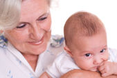Elderly woman holding a newborn in her arms — Stock Photo