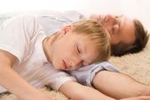 Dad and son sleeping on the carpet — Stock Photo