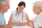 Woman doctor and an elderly couple — Stock Photo