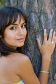 Girl leaning against the tree — Stock Photo