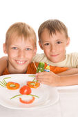 Boys holding a plate with vegetables — Stock Photo