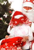 Santa gives presents to child — Stock Photo
