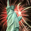 Statue of Liberty and fireworks in black sky - Stock Photo