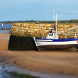 Small boat at ebb tide waiting for the rising water - Stock Photo