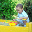 Baby plays with toys in sandbox — Stock Photo #6674672