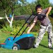 Stock Photo: Little Boy Gardener mowing the lawn