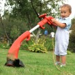 Young baby boy with trimmer in garden — Stock Photo #6740417
