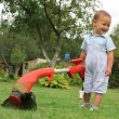 Young baby boy with trimmer in garden — Stock Photo