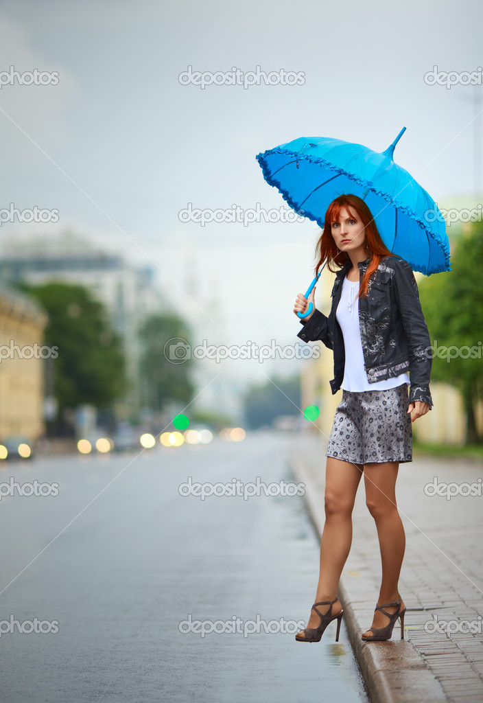 Redhead girls with umbrella waiting a bus — Stock Photo #6381329