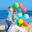 Children playing with balloons at the beach — Stock Photo