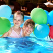 Stock Photo: Kids playing with balloons in swimming pool.