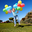 Kid playing with balloons in park. - Stock Photo