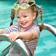 Baby in protective goggles leaves pool. — Stock Photo #5736226