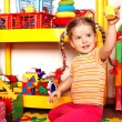 Stock Photo: Child with puzzle and wood block in play room.