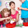 Children painting with teacher. — Stockfoto