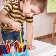 Child with pencil in play room. - Stock Photo