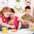 Foto Stock: Children painting with teacher.