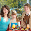 Family with child eating in cafe. — Stock Photo