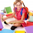 Stock Photo: Happy sitting schoolgirl in eyeglasses with pile of books.
