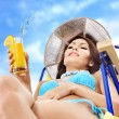 Stock Photo: Girl in bikini drinking orange juice.