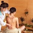 Woman getting massage in bamboo spa. - Stok fotoğraf