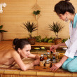 Woman getting massage in bamboo spa. - Zdjęcie stockowe