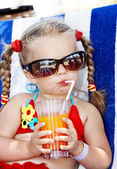Child in glasses and red bikini drink juice. — Stock Photo