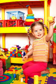 Child with puzzle and wood block in play room. — Stock Photo