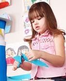Serious child cutting paper. — Stock Photo