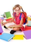 Siedzący szczęśliwy uczennica w okulary stos książek. — Zdjęcie stockowe