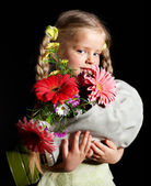 Child holding flowers and gas mask . — Stock Photo