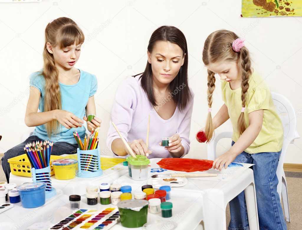 Child painting in preschool. Teacher help by little girl. — Stock Photo #5737610