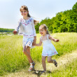 Kids running across green grass outdoor. — Stock Photo