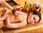 Woman getting massage in bamboo spa. — Photo