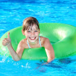 Child sitting on inflatable ring thumb up. — Stock Photo