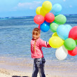 Child playing with balloons at the beach — Stock Photo #5972595