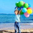 Stock Photo: Child playing with balloons at beach