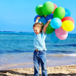 Child playing with balloons at beach — Foto Stock #5972600