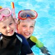 Kids in swimming pool learning snorkeling. - Stock Photo
