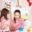 Child painting with teacher in preschool. — Stock Photo #5972700