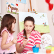 Stock Photo: Child painting with teacher in preschool.