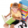 Stock Photo: Schoolgirl reading pile of books.