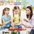 Kids painting in preschool. - Stockfoto