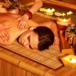 thumbnail of Woman getting massage in bamboo spa.