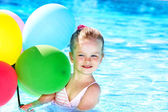 Child playing with balloons in swimming pool. — Stock Photo