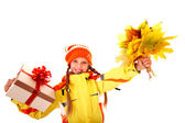 Child holding orange leaves and gift box. — Stock Photo